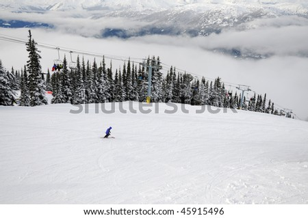 Skier going down the hill and people riding a chairlift at Whistler-Blackcomb ski resort in Canada
