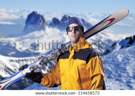 skier holding a pair of skis looking at the mountains.