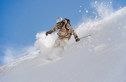 Skier in deep snow. In turn raises the snow dust.
