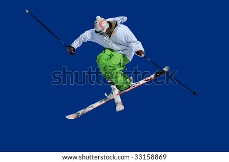 skier in green and white clothes performing a tele-heli with skis crossed at the same time as executing a full spin (in this shot, facing backwards) isolated against a blue background