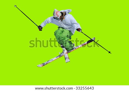 skier in green and white clothes performing a tele-heli with skis crossed at the same time as executing a full spin (in this shot, facing backwards) isolated against a green background