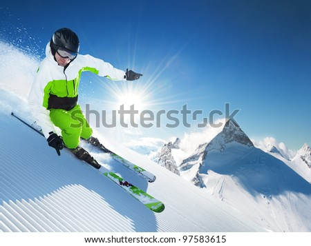 Skier in high mountains at sunny day