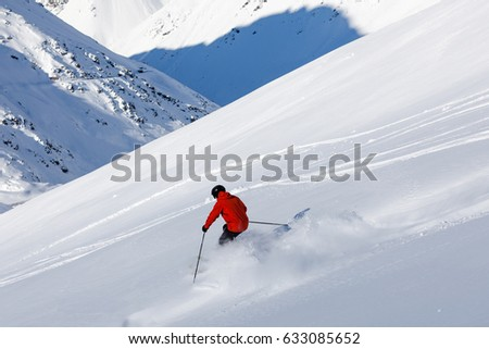 Skier in orange jacket and black helmet on the fresh snow covered slopes of Portillo mountain resort #633085652