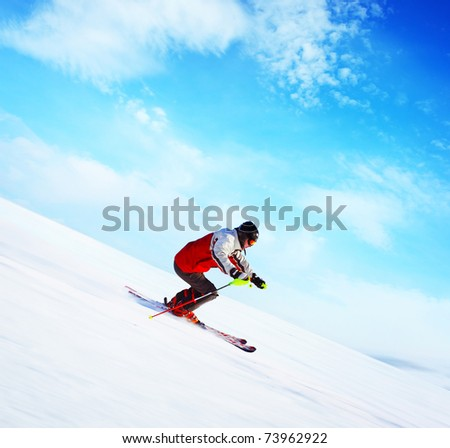 Skier in red jacket riding on hill. Motion blurred snow and cloudy blue sky