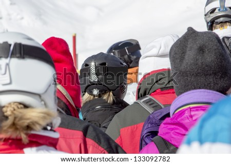 skier in ski region standing in line in front of a lift station