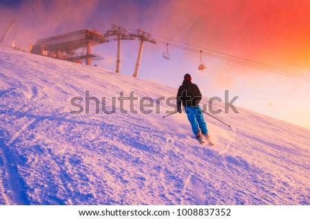 Skier in ski resort. Red sunset sky in background. #1008837352