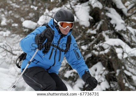 Skier is free riding between trees