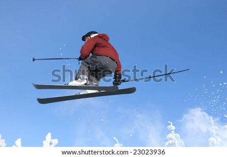 Skier jumping in fresh snow and sun - stock photo