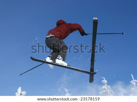 Skier jumping with a ski coming off mid-air