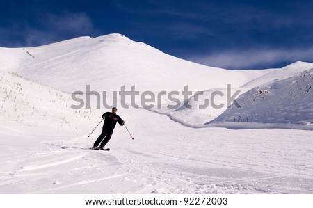 Skier man going down on slope in sunny day