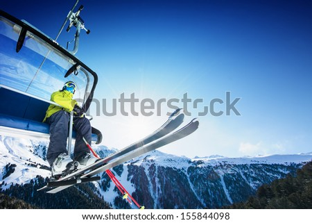 Skier on lift in mountains