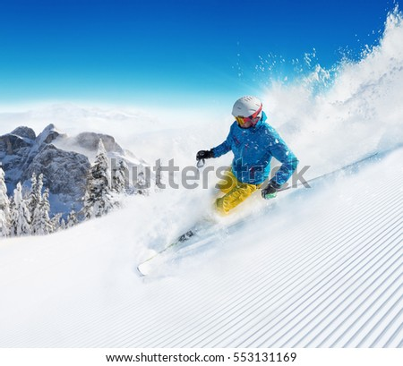 Skier on piste running downhill in beautiful Alpine landscape. Blue sky on background. Free space for text #553131169