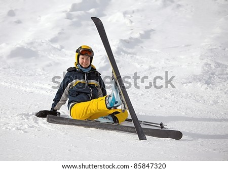 Skier resting sitting in the snow
