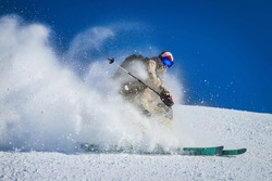 Skier rides beautifully in the mountains Skier rides fast and snow flies
