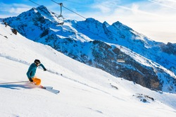 Skier rides down the slope in Alps mountains. Winter sport. Val Thorens, 3 Valleys, France. Beautiful mountains, winter landscape