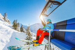 Skier sitting at ski chair lift in beautiful sunny day, Alpine mountains. Concept of skiing