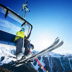 Skier sitting at ski lift in high mountains