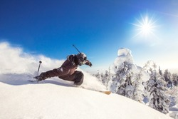 Skier skiing downhill during sunny day fresh snow freeride. Extreme High speed, frosty dust scatters.