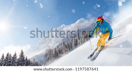 Skier skiing downhill during sunny day in high mountains #1197587641