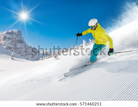 Skier skiing downhill during sunny day in high mountains #571460251