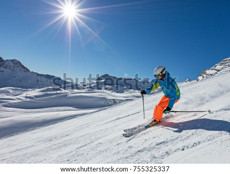 Skier skiing downhill during sunny day in high mountains #755325337