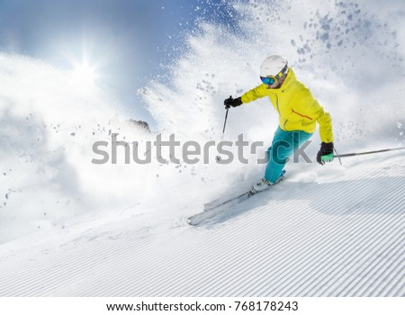Skier skiing downhill during sunny day in high mountains #768178243