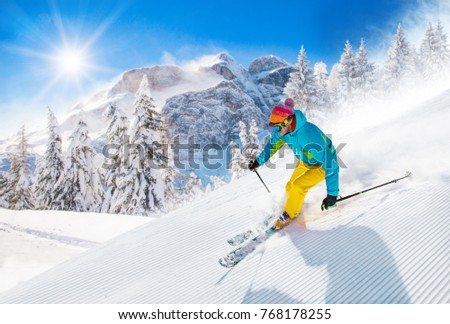 Skier skiing downhill during sunny day in high mountains #768178255