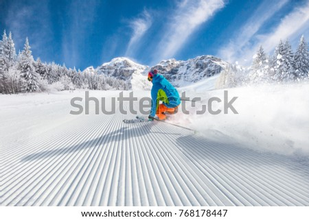 Skier skiing downhill during sunny day in high mountains #768178447