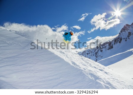 Skier skiing downhill in high mountains #329426294