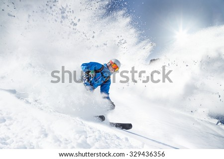 Skier skiing downhill in high mountains #329436356