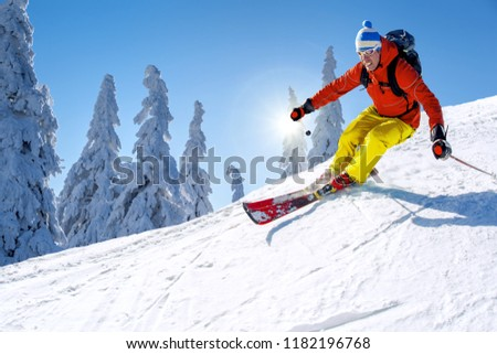 Skier skiing downhill in high mountains against blue sky #1182196768
