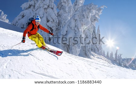 Skier skiing downhill in high mountains against blue sky #1186883440