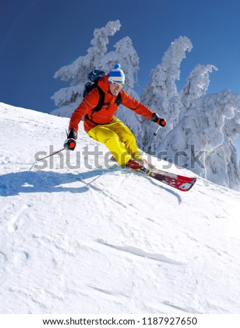 Skier skiing downhill in high mountains against blue sky #1187927650