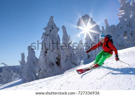 Skier skiing downhill in high mountains against blue sky #727336936