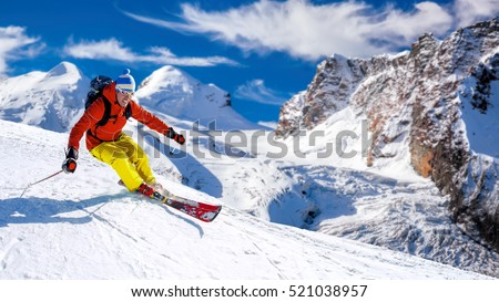 Skier skiing downhill in high mountains against sunshine #521038957