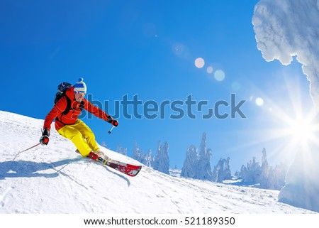 Skier skiing downhill in high mountains against sunshine #521189350