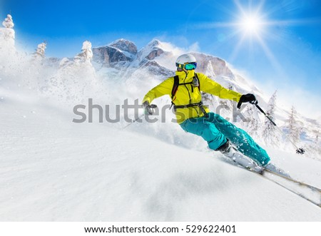 Skier skiing downhill in high mountains during sunny day. #529622401