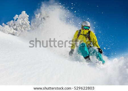 Skier skiing downhill in high mountains during sunny day. #529622803