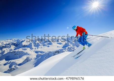 Skier skiing downhill in high mountains in fresh powder snow. Snow mountain range in background. Mt Fort Peak Alps region Switzerland. #479896576