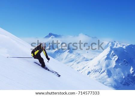 Skier skiing downhill in high mountains, Solden, Austria