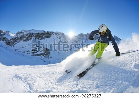 skier skiing downhill on fresh powder snow  with sun and mountains in background #96275327