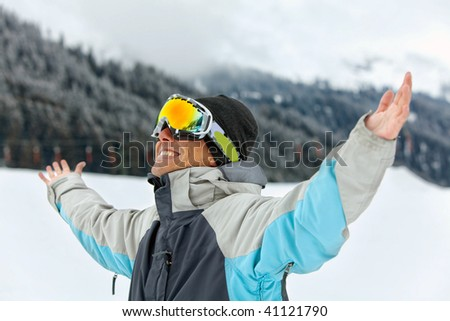 skier smiling full of joy with his arms up