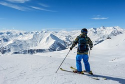 Skier standing in front of mountains