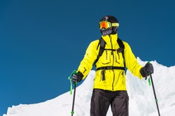 Skier standing on a slope. Man in a light suit, the helmet and mask in skiing is to ski. In the background snow-capped mountains , skiers . Caucasus Mountains, Elbrus, Russia
