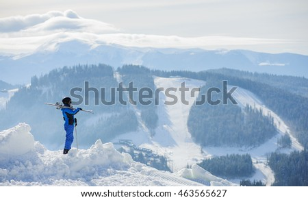 Skier standing on top of the mountain and enjoying the view on beautiful winter mountains on a sunny day. Woman is wearing blue ski suit, holding skis on her shoulder. Carpathian Mountains, Bukovel