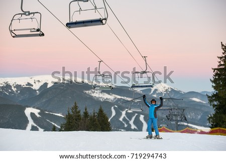 Skier woman in blue winter clothes, helmet and goggles raised sticks up standing under ski-lift on a background of ski resort and snow mountains #719294743