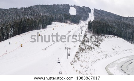 Skiers and snowboarders go down the slope in a ski resort Bukovel, Ukraine. #1083867017