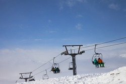 Skiers and snowboarders go up on chair-lift, snowy off-piste ski slope and high mountains in fog at sun winter day. Caucasus Mountains, Georgia, region Gudauri.