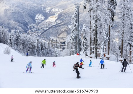Skiers and snowboarders riding on a ski slope in Sochi mountain resort on snowy winter background