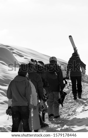 Skiers and snowboarders with skis and snowboards go up on snowy road at sun winter morning. Caucasus Mountains, Georgia, region Gudauri. Black and white toned image with copyspace.   #1579178446